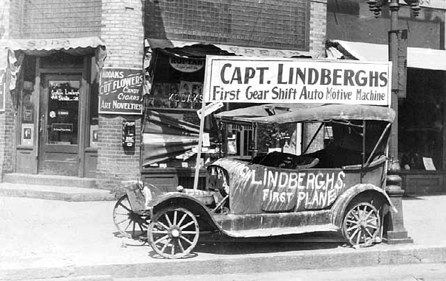 Old car with sign 'Capt. Lindberghs first gear shift auto motive machine'