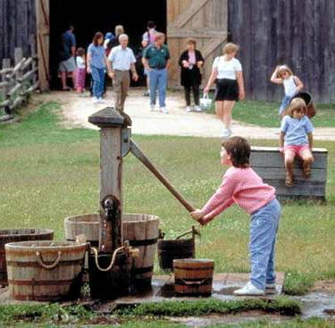 A young visitor pumps water to carry to the animals.